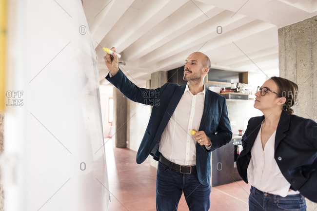 Businessman writing on whiteboard while standing by woman at office