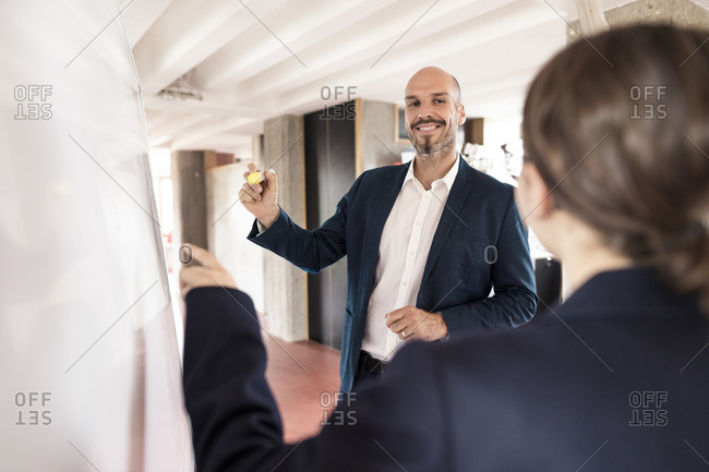 Business people having discussion while writing on whiteboard at office
