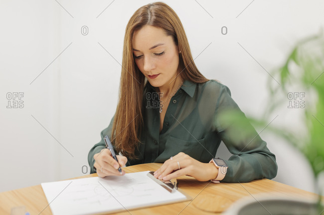 Female psychologist working while sitting at office