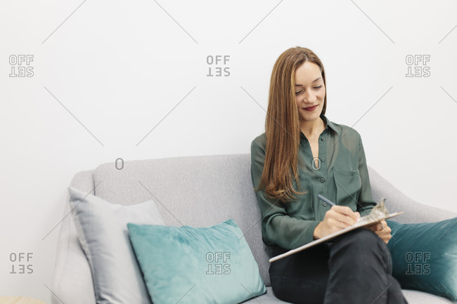 Smiling psychologist working while sitting on couch at office