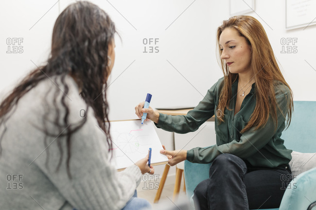 Psychologist explaining chart with note pad while sitting by patient at office