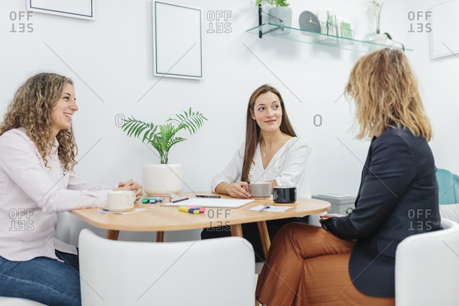 Women having coffee while sitting at office