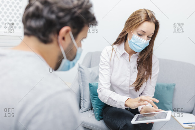 Doctor wearing face mask using digital tablet while sitting by man at office