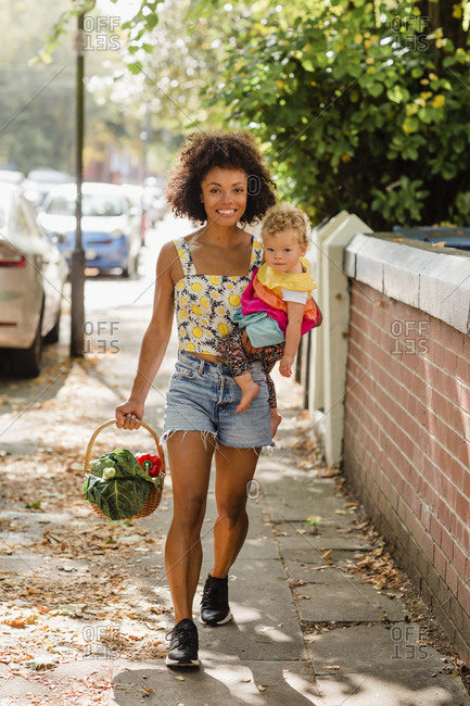 Smiling mother carrying baby and vegetable basket while walking in city