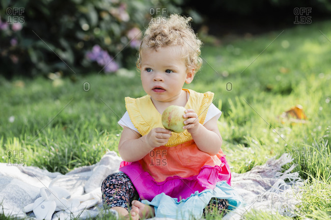 Cute baby girl holding fruit while sitting on grass at park