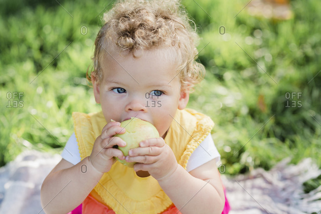 Cute baby girl eating fruit while sitting on grass at park
