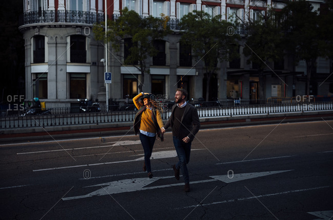 Husband and wife holding hand while crossing road in city