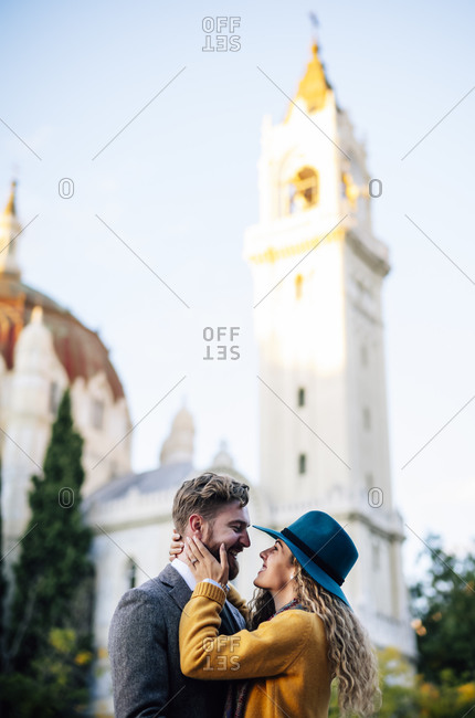 Man and woman doing romance while standing against church
