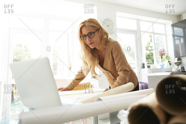 Mature woman with map working on laptop while standing at home