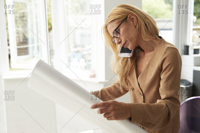 Mature woman talking on smart phone holding map while sitting at home in kitchen
