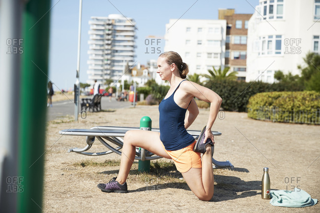 Female athlete doing stretching exercise in outdoor gym on sunny day