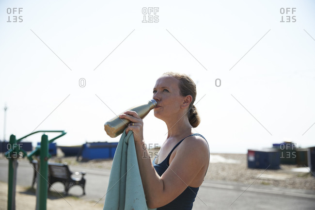 Mature woman drinking water while standing in outdoor gym on sunny day