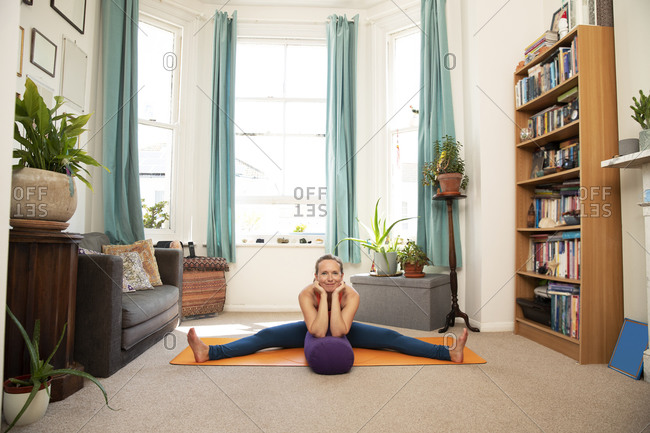 Smiling woman with hand on chin doing stretching exercise at home