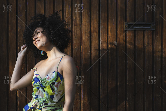Young woman looking away while toughing hair standing against wooden wall
