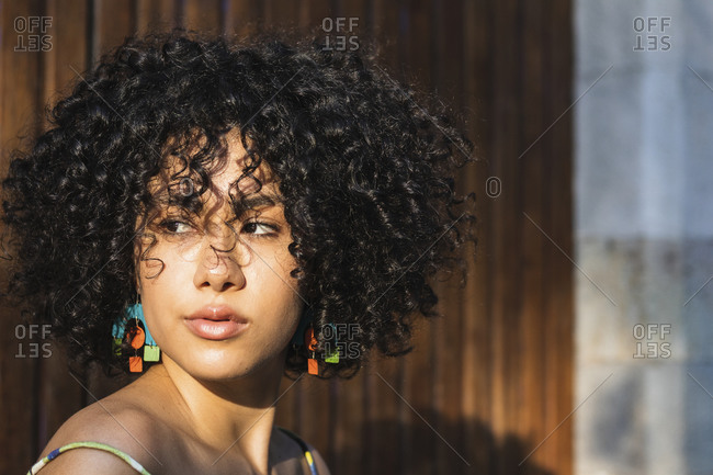 Curly hair woman looking away while standing against wooden wall