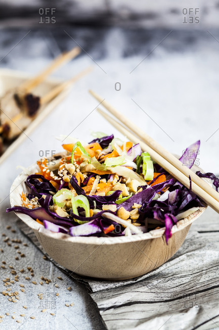 Vietnamese cabbage salad garnished with shredded chicken and peanut on table outdoors