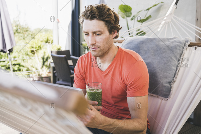 Mid adult man using digital tablet holding juice while sitting at home