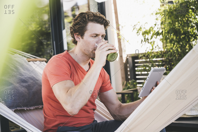 Mid adult man using digital tablet drinking juice while sitting at home