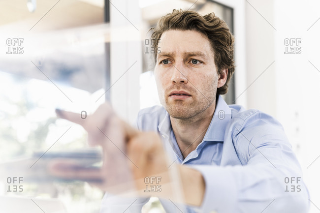 Mid adult man pointing on glass material while sitting in office