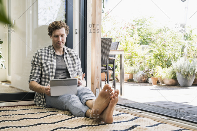 Mid adult man holding juice glass using digital tablet while sitting at home