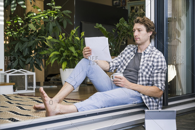 Mid adult man with coffee cup holding paper while sitting at home
