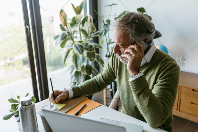 Mature man talking on mobile phone while working at home