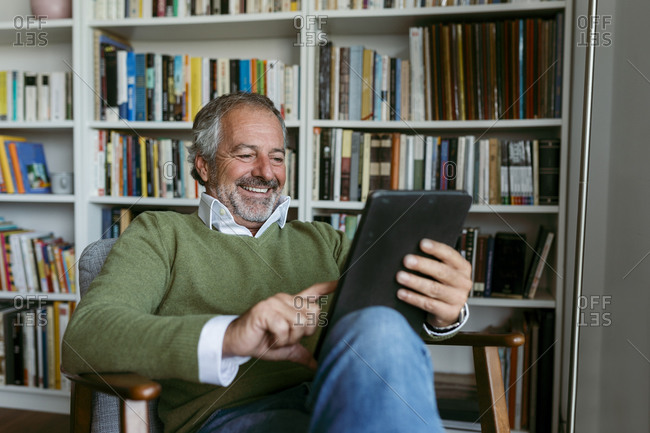Smiling man using digital tablet while sitting against bookshelf at home