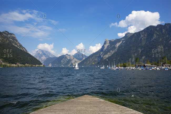 Austria- Upper Austria- Ebensee- Slipway on shore of Traunsee lake with boats and mountains in background