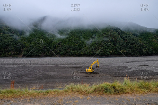 Wakayama, Japan - November 18, 2017: Bulldozer in a field in front of fog covered mountains