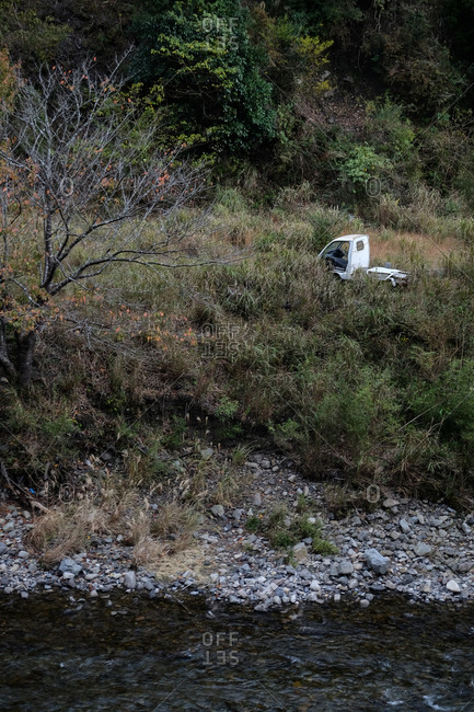 Abandoned truck in tall grass on mountainside riverbank