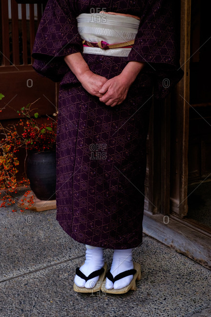 Low-section of a woman dressed in typical Japanese kimono and geta sandals