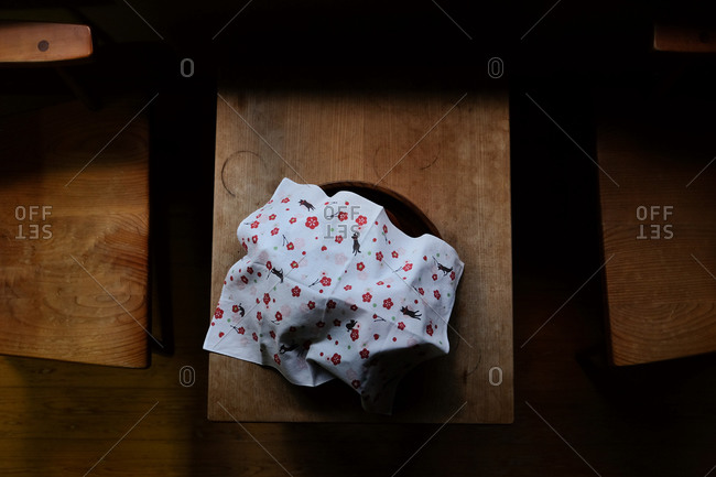 Overhead view of a plate covered with a floral and cat linen napkin