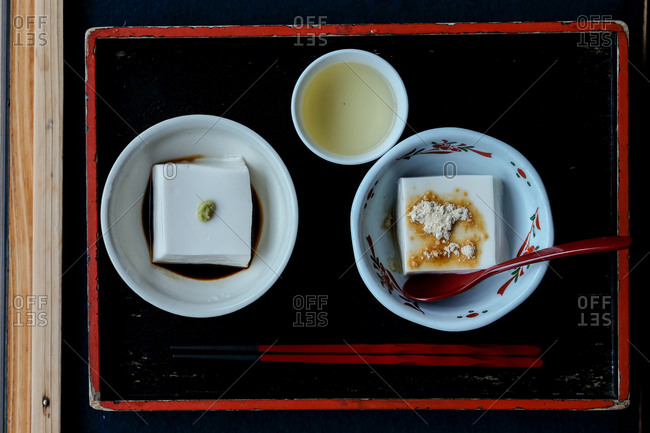 Overhead view of a Japanese tofu dish served on red and black tray