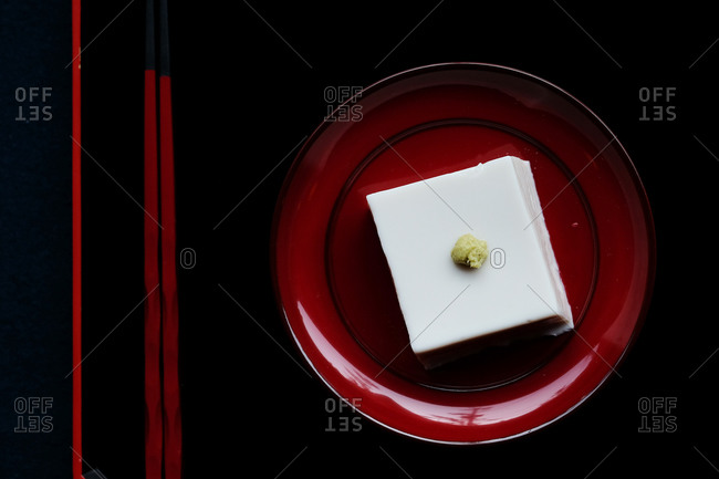 Overhead view of a Japanese tofu dish served on red plate and black tray