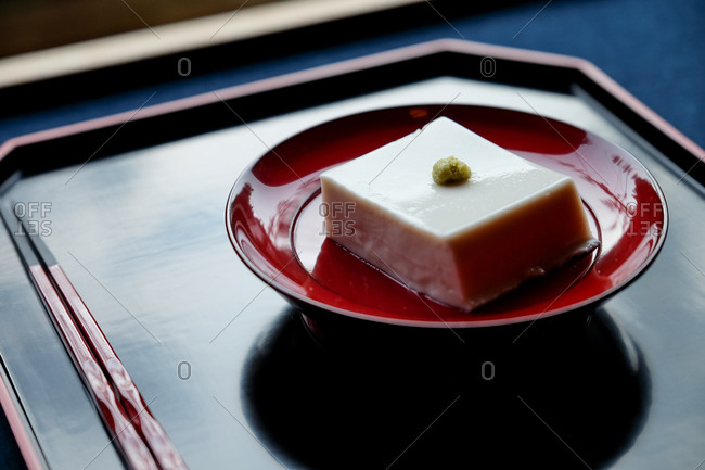 Close up of a Japanese tofu dish served on red plate and black tray