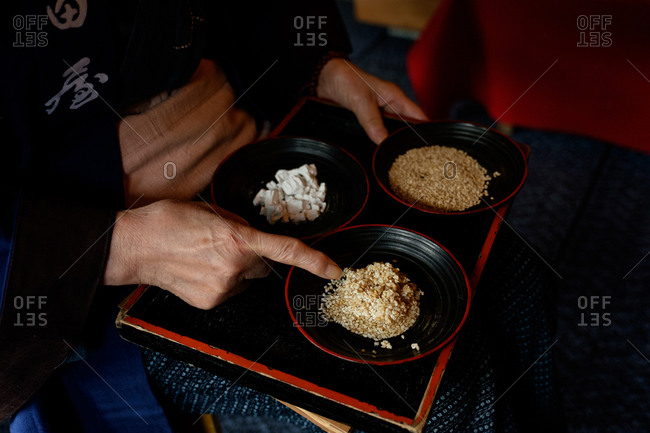 Person dressed in traditional Japanese kimono pointing to sesame seeds in a bowl