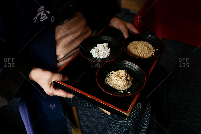 Person dressed in traditional Japanese kimono holding a tray with tofu and sesame seeds