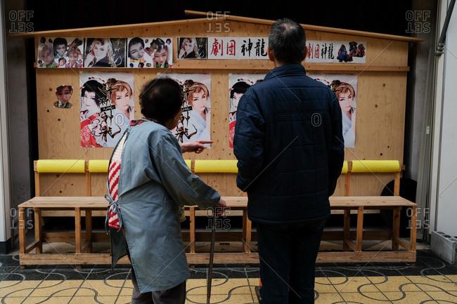 Wakayama, Japan - November 21, 2017: Rear view of couple looking at Japanese advertisements while shopping