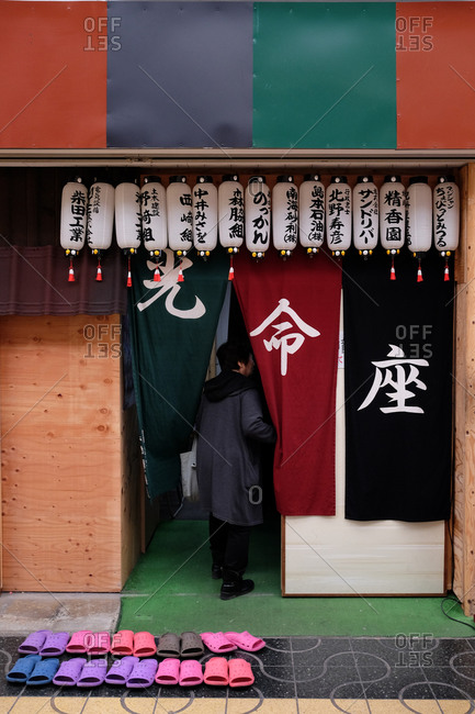 Wakayama, Japan - November 21, 2017: Rear view of woman walking into building with Japanese symbols and lanterns with slippers arranged neatly outside