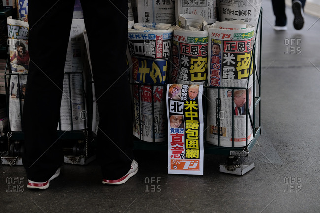 Wakayama, Japan - November 21, 2017: Legs of a person standing at a newspaper stand on city street