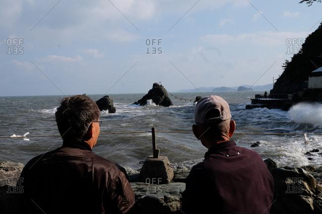 Two men overlooking Futamiokitama Shrine off the coast of Futami, Mie, Japan