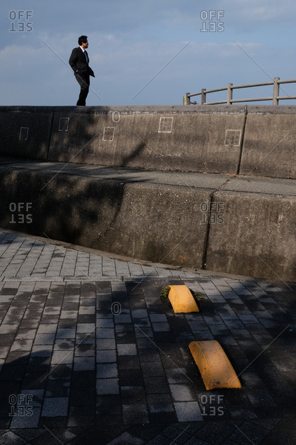 Wakayama, Japan - November 22, 2017: Man in suit standing on concrete wall looking away in deep thought