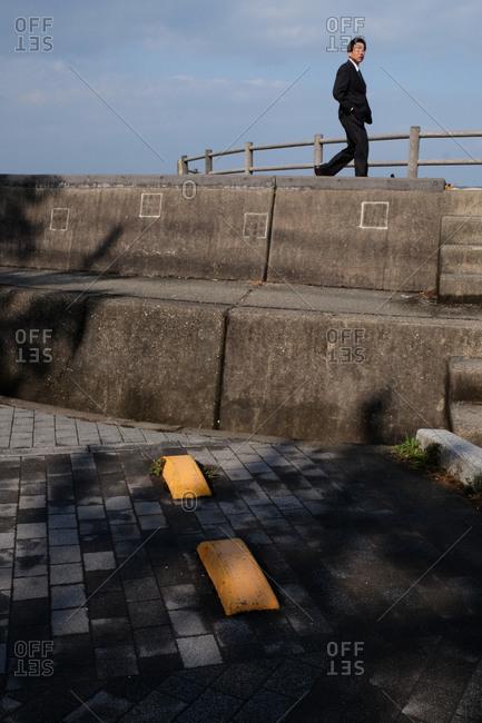 Wakayama, Japan - November 22, 2017: Man in suit walking on top of a concrete wall