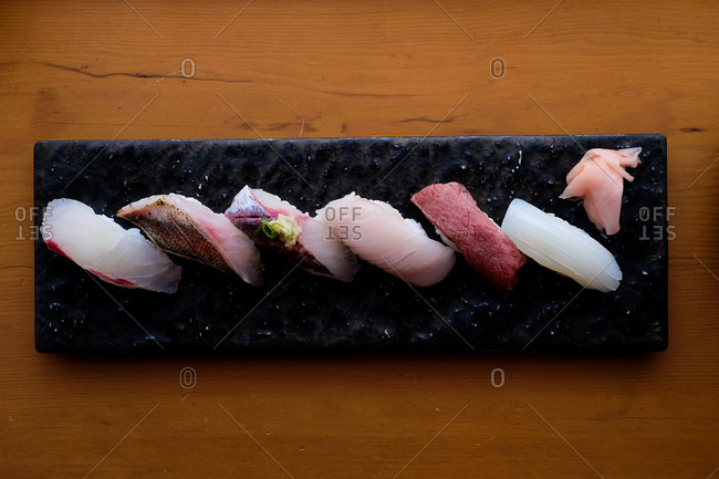 Sashimi seafood dish on a slate tray on wooden table viewed from above