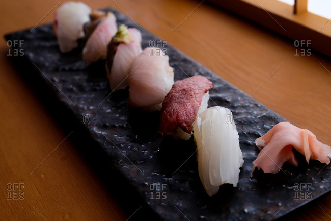 Close up of a sashimi seafood dish on a slate tray on wooden table viewed from above