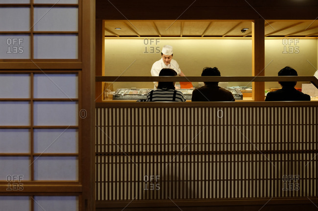 Wakayama, Japan - November 22, 2017: Looking into a sushi restaurant with chef working and people sitting and dining in