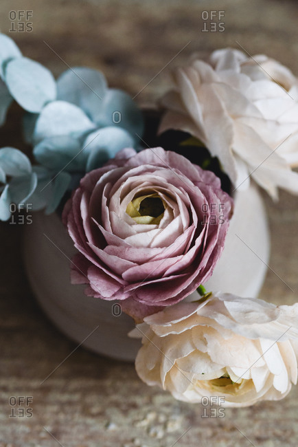 Sugar flowers made for cake decorating inside of ceramic cup viewed from above on rustic table