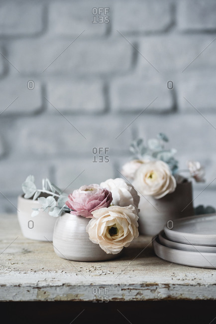 Sugar flowers made for cake decorating inside of ceramic cup on a rustic table