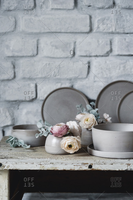Set of handmade ceramic plates and bowls with sugar flowers for cake decorating