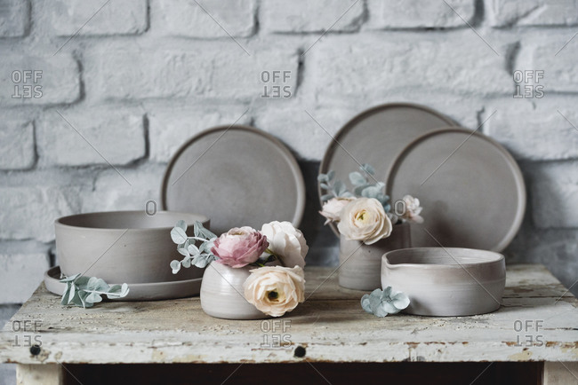Set of handmade ceramic plates and bowls with sugar flowers for cake decorating on a rustic table